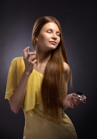 beautiful young woman spraying perfume on gray dark  background