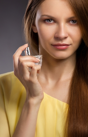 Close up portrait  of a beautiful young woman spraying perfume on gray dark background photo