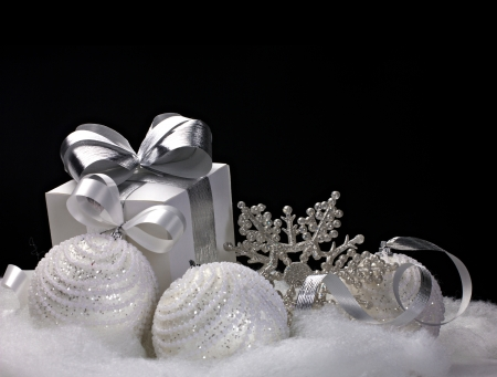 black ribbon bow: White Christmas balls, gift, snowflake - still life on black background