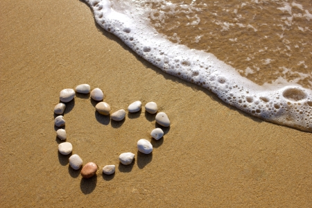 heart-shaped stones on a beach with sufr wave photo