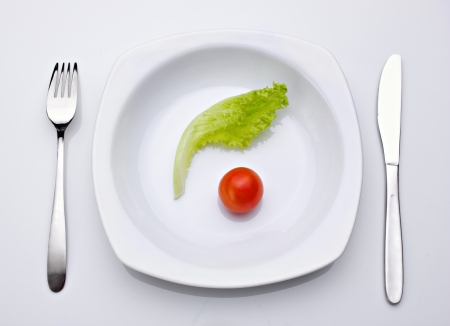 salad and tomato in plate,  fork and knife near plate on  light background Stock Photo - 16910768
