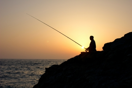 recreate: angler on sunset fishing on sea
