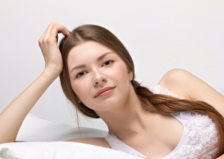 beautiful young woman in a bed on white background Stock Photo - 17230323