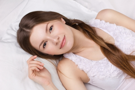 beautiful young woman in white pajamas on a white bedding Stock Photo - 17239475