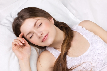 beautiful young woman sleeping in a white pajamas photo