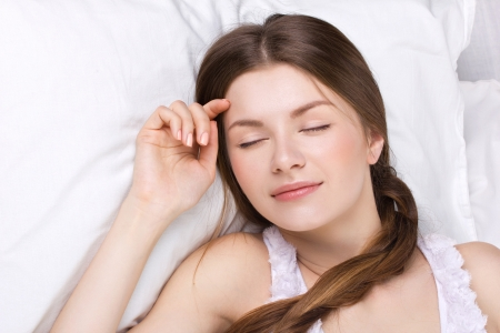 beautiful young woman dreaming in white pillow photo