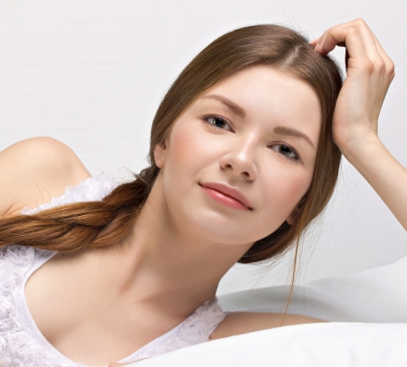 beautiful young woman in a bed on white background photo