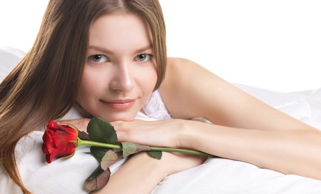 beautiful  young woman in a bed with red rose on white background Stock Photo - 17255238