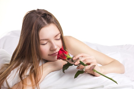 young beautifu woman with fresh red rose in a bed on white background photo
