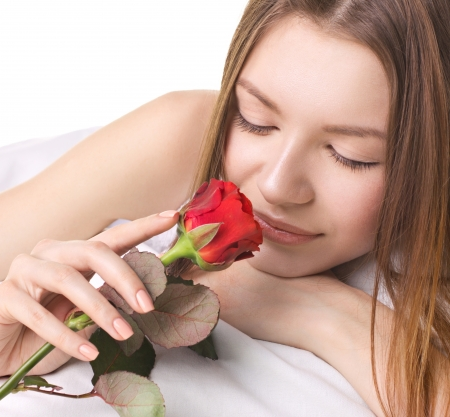 close-up portrait of beautiful young woman with red rose in a bed on white background photo