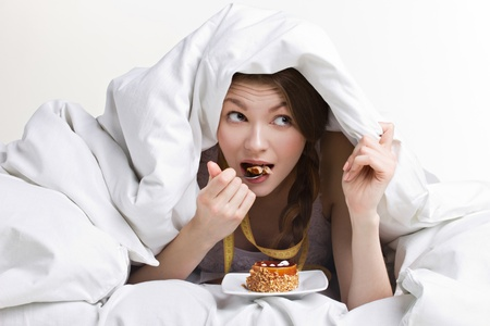 furtively: young beauty woman eating dessert under cover on white background