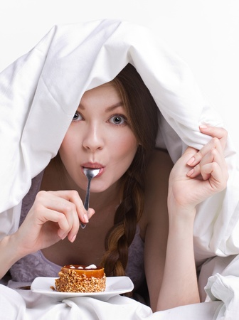 furtively: girl on diet eating spoon instead of dessert  under white cover on white background