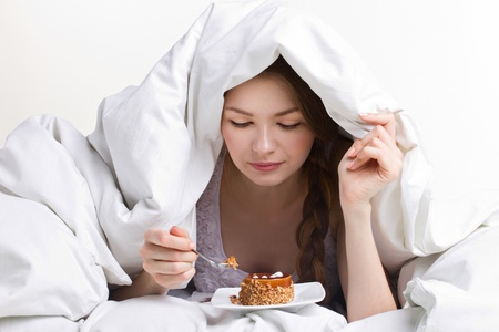 young beauty girl on diet eating s dessert  under white cover on white background Stock Photo - 17255228