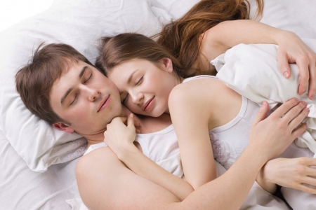 young husband and  wife sleepping in white beg