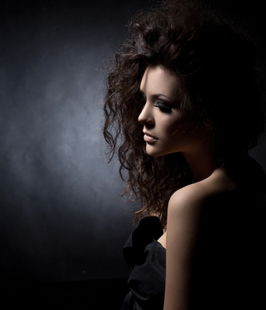 portrait of a glamorous girl in black  dress on dark background photo