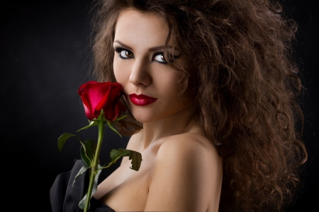 sensual lips: closeup portrait of a glamorous young womanl  with red rose on dark background