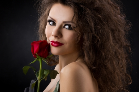 closeup portrait of a gorgeous young womanl  with red rose on dark background photo