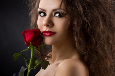 closeup portrait of a glamorous beautiful woman with red rose on dark background photo