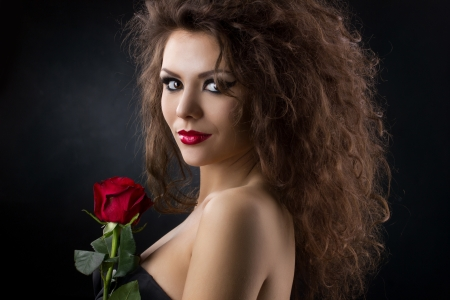 attractive gorgeous: beautiful young woman with red rose on dark background