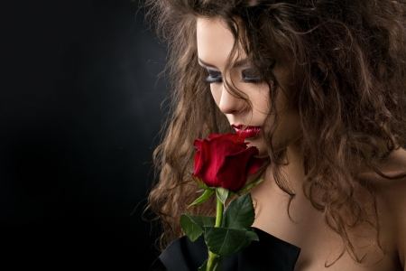 attractive gorgeous: glamorous young woman with red rose on dark background