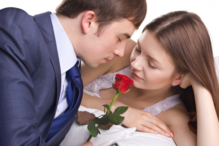 businass man present a red rose to beautiful girl on white background photo
