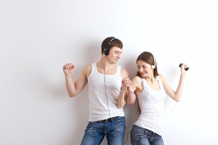 woman listening to music: boy and girl  listening of a music and dancing on wall background