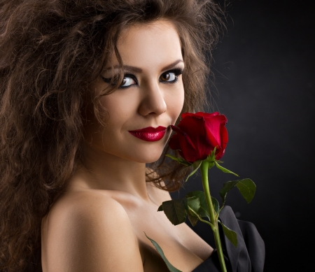 glamorous young woman with rose on dark background photo