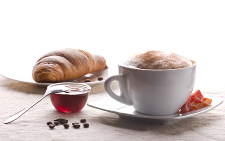 coffee with cream and cinnamon, croissant, jam,  and candied fruits on white background photo