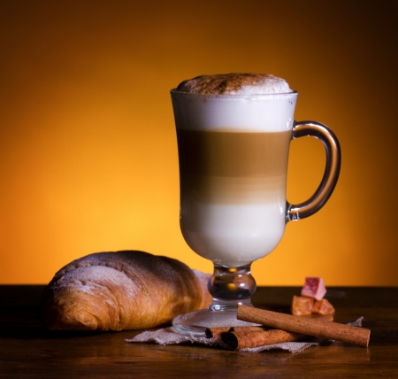 latte macchiato: latte macchiato with cinnamon and croissant on wood table on yellow-brown  background
