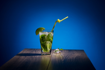 alcoholic beverage with tropical fruit, ice and mint on wooden table on blue background photo