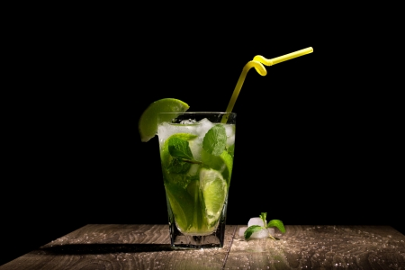 fresh coctail with citrus fruit, mint and ice on wooden table on black background