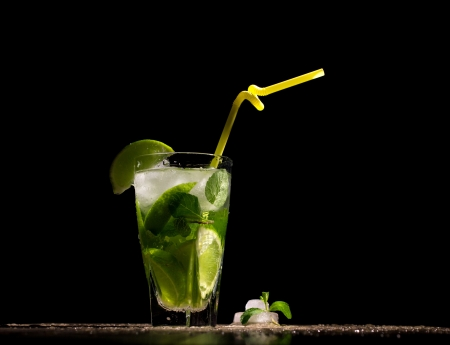 alcoholic beverage with tropical fruit, ice and mint on wooden table on black  background photo