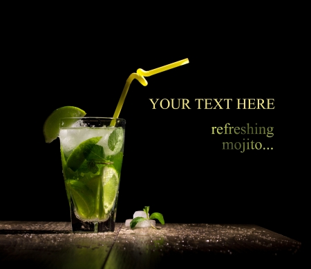 mojito: fresh drink with lime, mint and ice on wooden table on black background