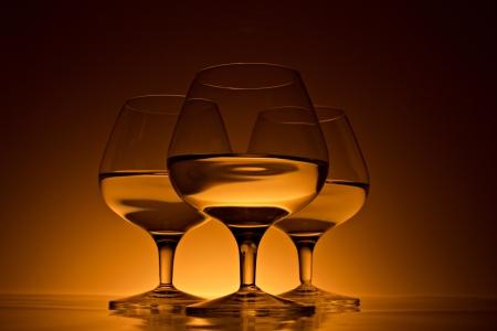 drunks: glass for brandy with golden beverage on dark-golden background