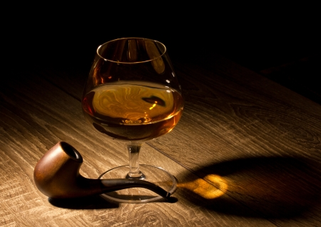 drunks: brandy in glass and tobacco pipe on wooden table