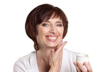 woman face cream: mature laughing woman with facial cream isolated on white Stock Photo