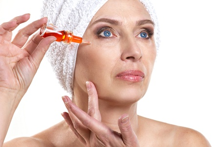 serum: mature woman doing rejuvenation  spa procedure for face on white background Stock Photo