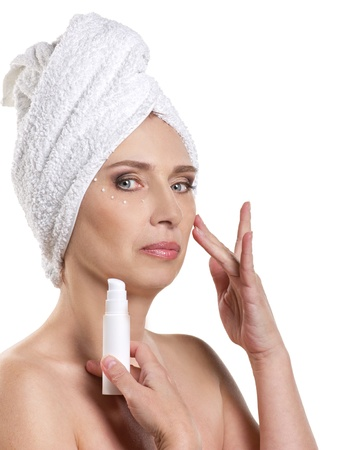 eye cream: mature woman in towel appling fassial cream on white background