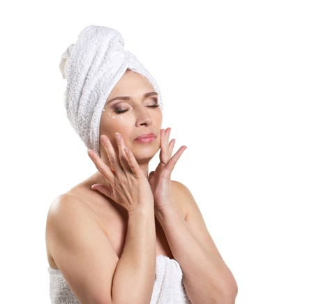 woman in towel applying cream and doing massage for face on white background