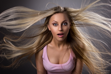 portrait of a amazed blond young woman with waving hair and opened mouth on grey-dark background Stock Photo