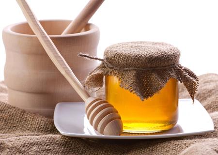Miele in vaso trasparente, drizzler e vaso di legno sul saccheggio su sfondo bianco closeup
