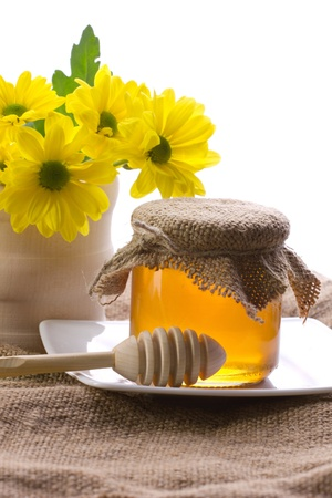 closeup of honey in pot, drizzler and yellow flowers in wooden jar on sacking, on white background photo