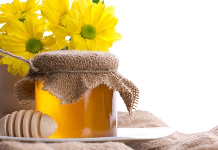 closeup of honey in glass pot, drizzler and yellow flowers in wooden jar on white background photo