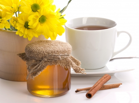 cold remedy: honey in pot, tea in cup, flower in wooden jar and stills of cinnamon isolated on white Stock Photo