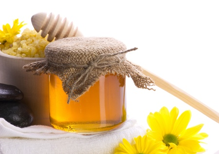 salts: spa still-life with honey. Stones, sea salts, towel, yellow flower and honey on white background