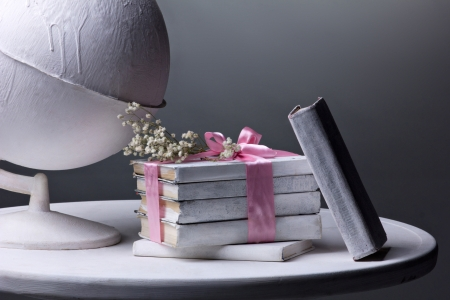 white globe, pile of old  books with pink bow and flowers on white round table, on grey background  photo