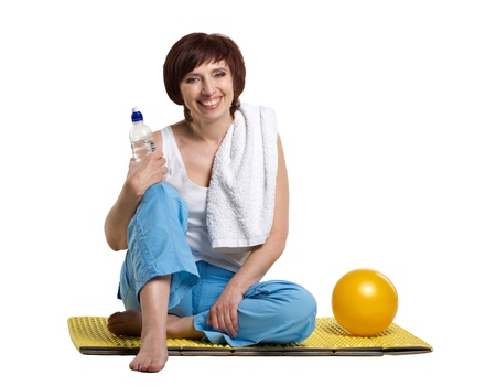 50 to 60: smiling woman sitting on yellow matting with bottle of water, near lieing  yellow ball, isolated on white Stock Photo