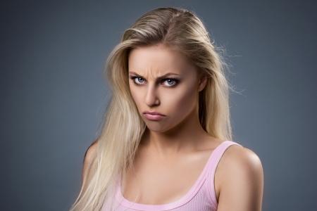 fille triste: portrait d'une belle jeune femme blonde mécontents sur fond gris foncé