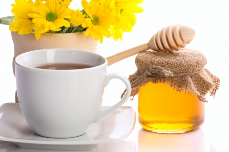 country still with tea, flowers  and honey on white background photo