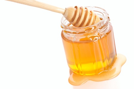 cold remedy: translucent honey and drizzler isolated on white